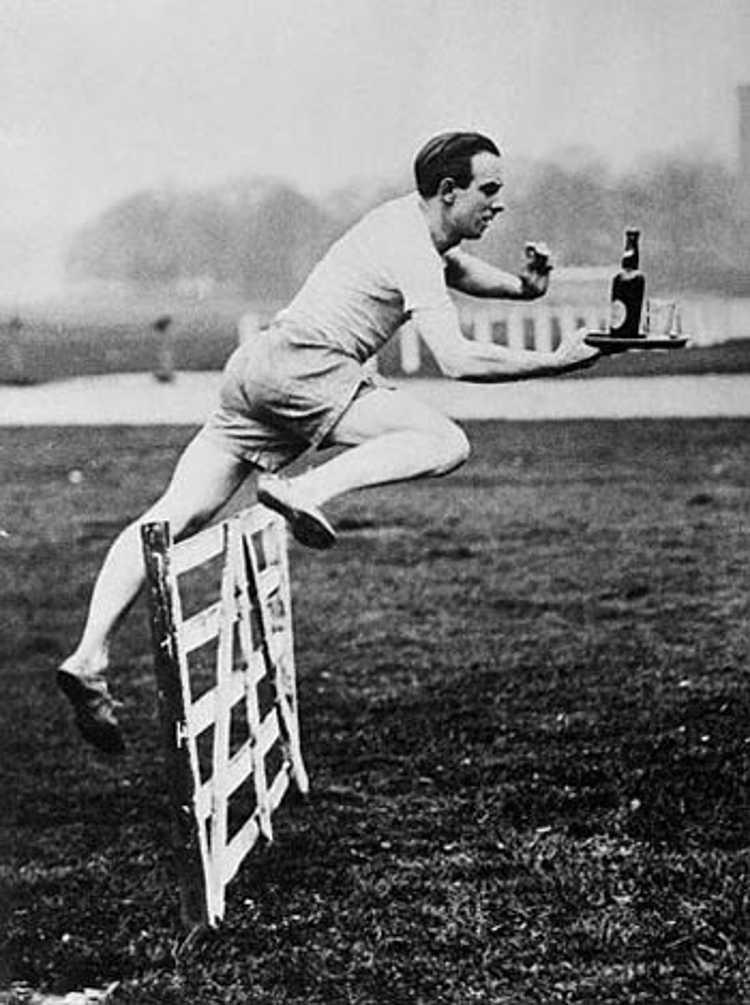 Mężczyzna skacze przez przeszkodę trzymając w ręce tacę z butelką