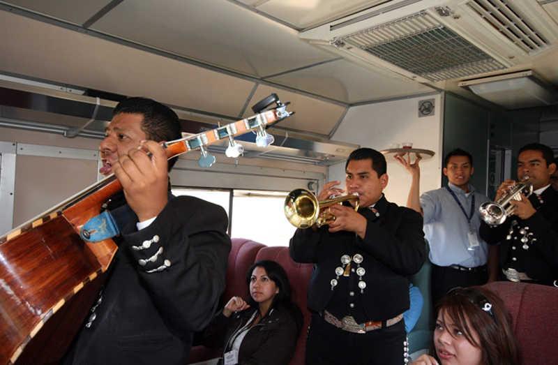 Muzycy Mariachi grają dla pasażerów na instrumentach