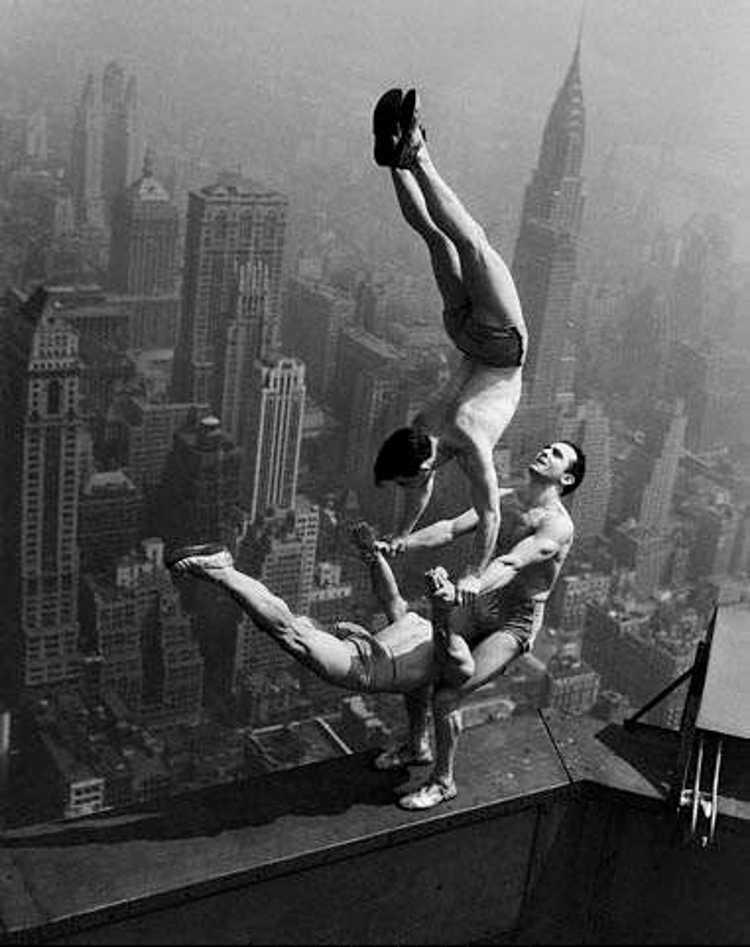 Troje akrobatów tworzą figurę na krawędzi dachu