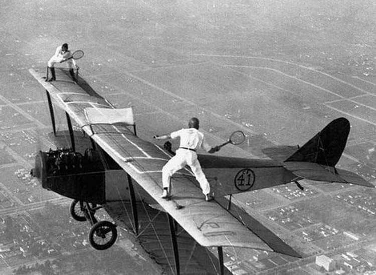 Dwóch mężczyzn, gra w tenisa na skrzydłach samolotu podczas jego lotu