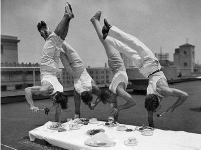 Mężczźni stojąc na jednej ręce jedzą posiłek