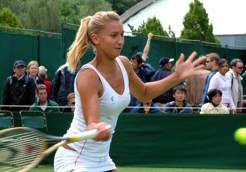 Dziewczyna w białym kostiumie gra w tenisa ziemnego