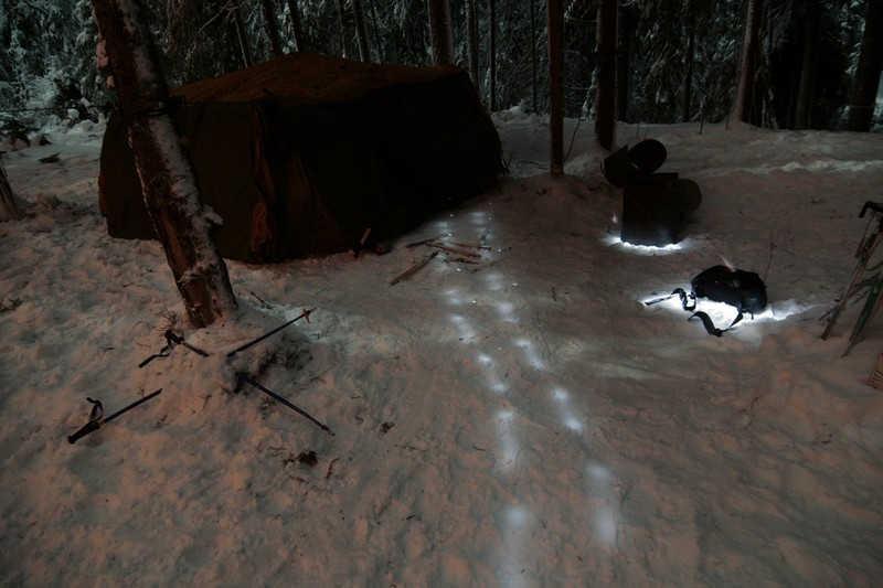 Podświetlane nocą ślady na śniegu.