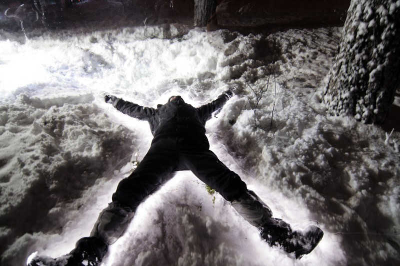 Podświetlona nocą leżąca postać na śniegu.
