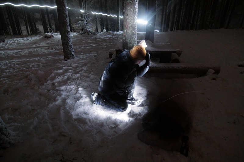Podświetlona klęcząca postać na śniegu w lesie.