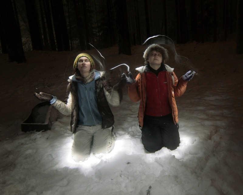 Podświetlone nocą dwie postacie w lesie zimą