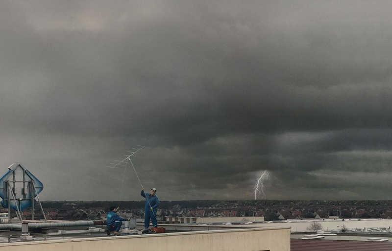 Monterzy ustawiają antenę na dachu