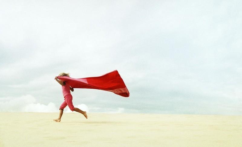 Biegnące dziecko z czerwonym materiałem