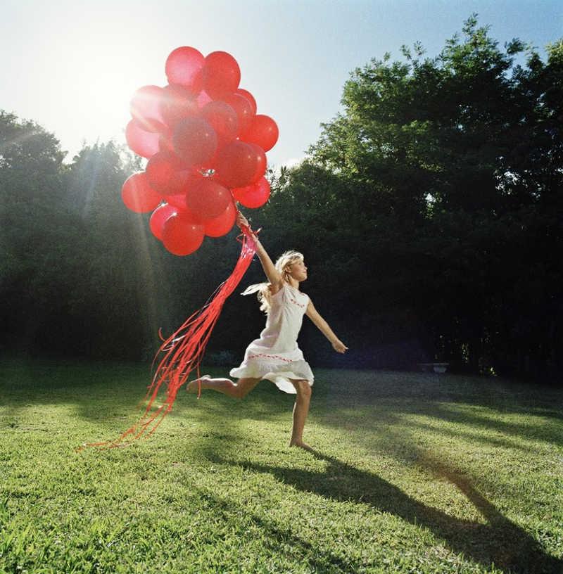Biegnąca dziewczynka z balonami