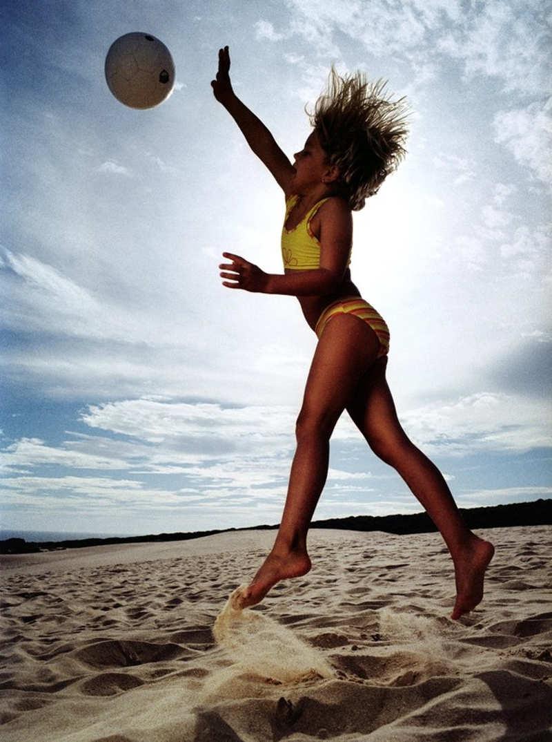 Mała dziewczynka gra w piłkę na plaży