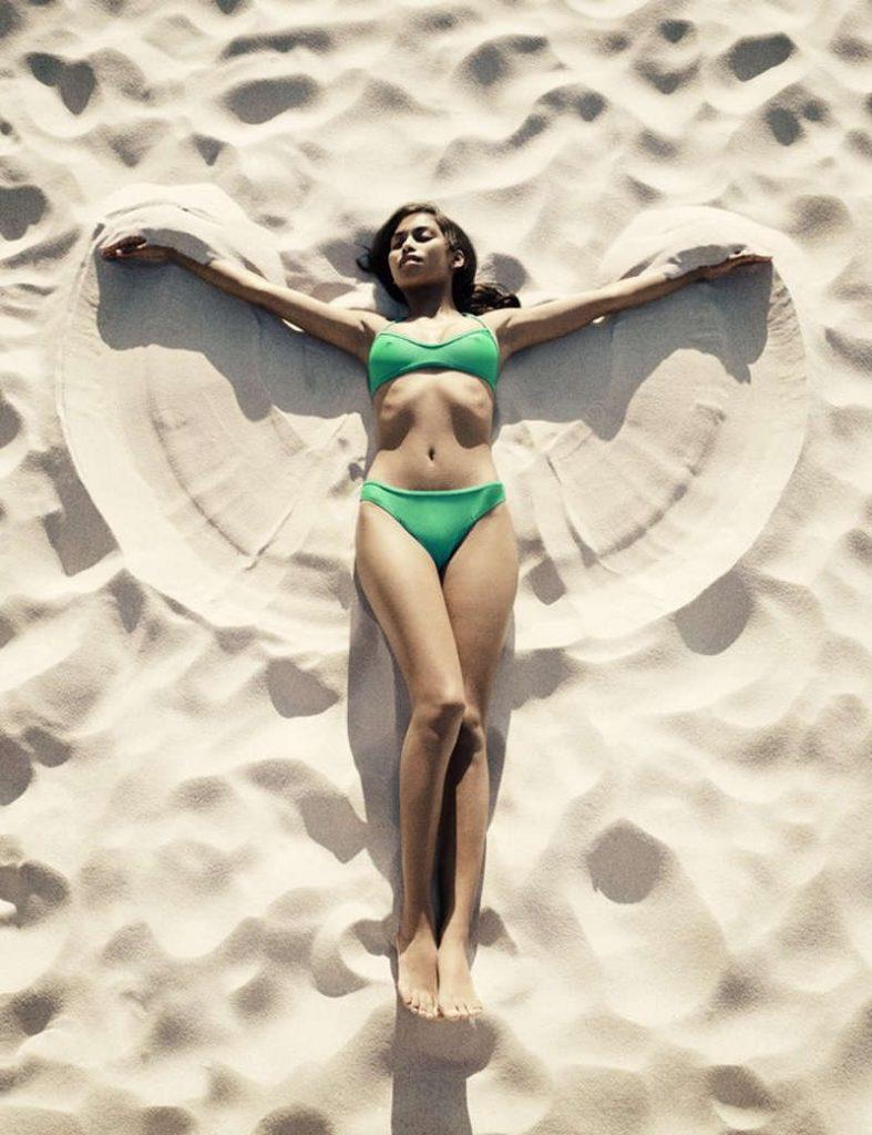 Brunetka leży na drobniutkim piasku na plaży