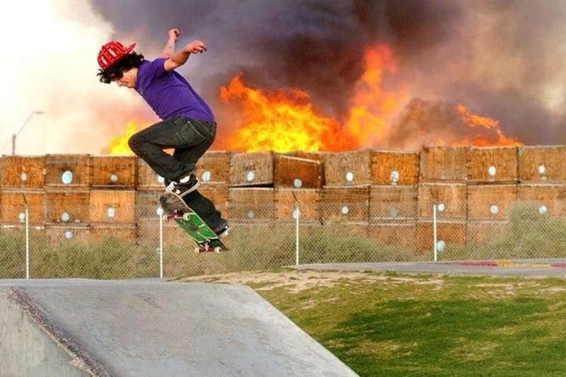 Chłopak jeżdżący na deskorolce na tle pożaru