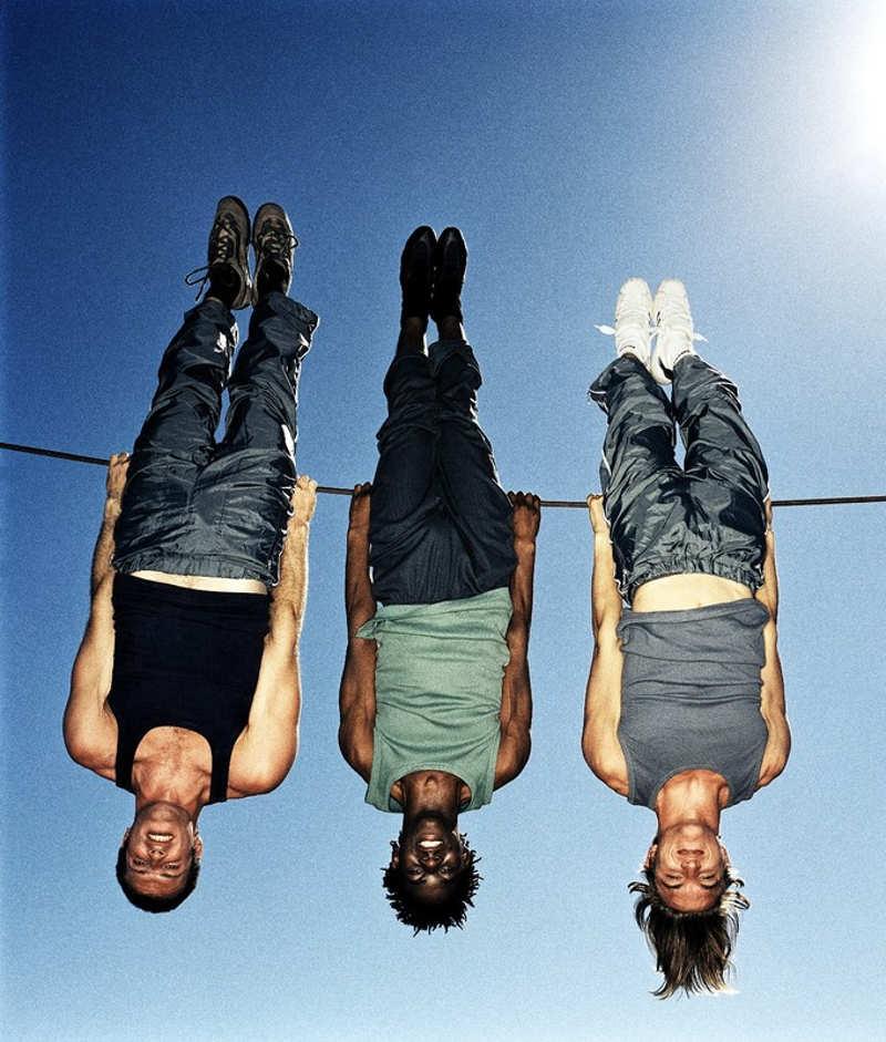Trzech mężczyzn wisi do góry nogami na linie