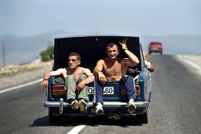 Dwóch mężczyzn jadą w bagażniku