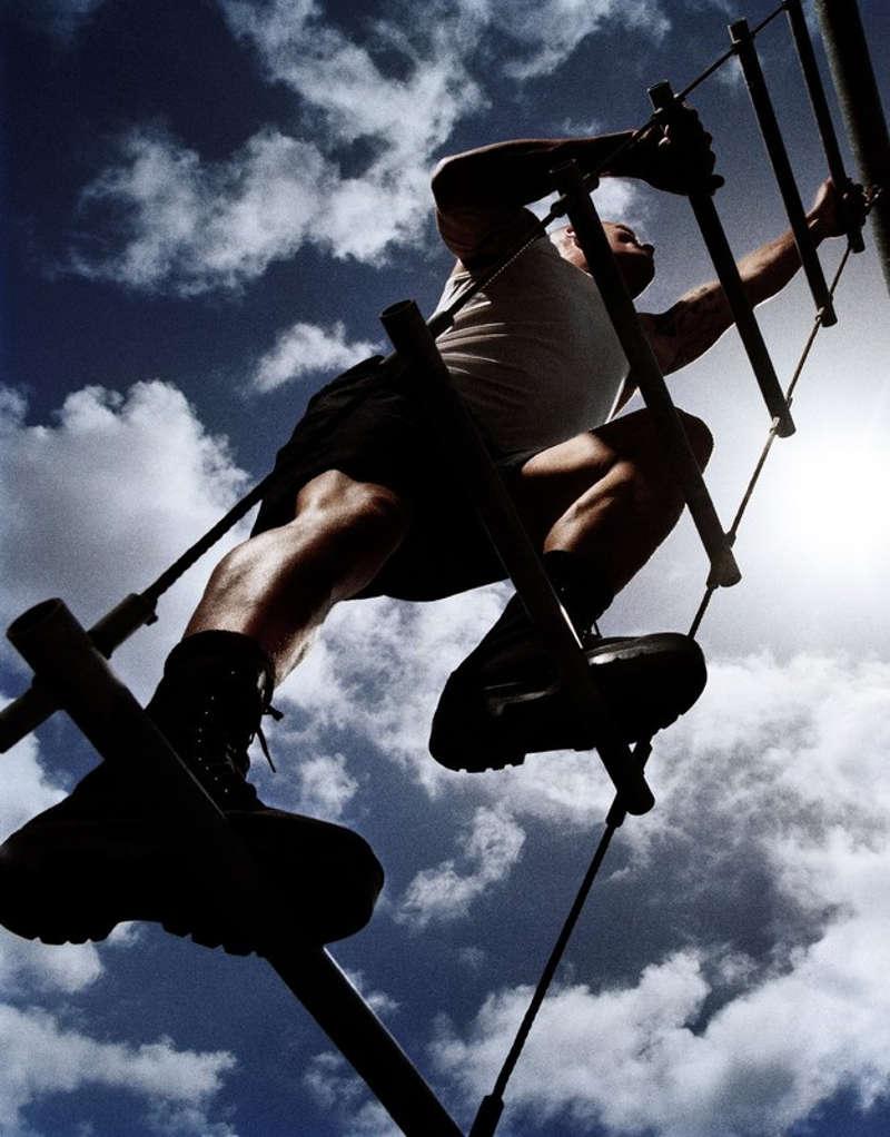 Człowiek w traperach wspina się po sznurowej drabince