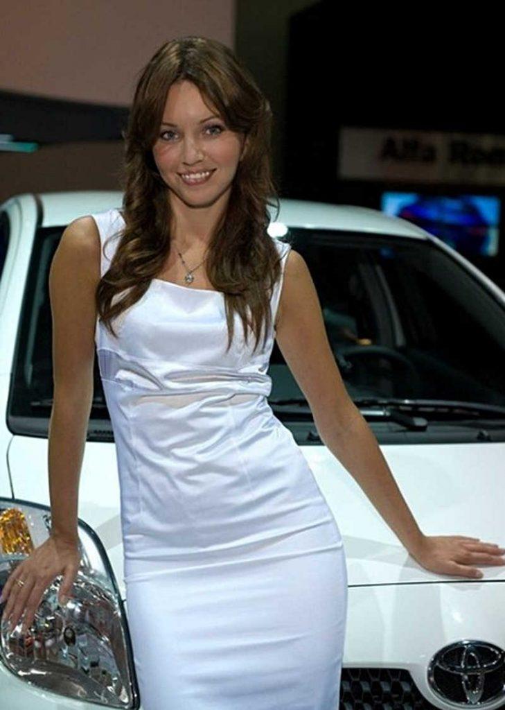 Brunetka w białej sukience na tle białego auta
