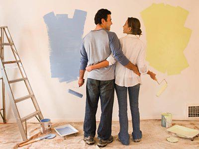 Para ludzi maluje ścianę
