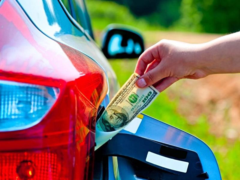 Kierowca wyciąga banknot z baku samochodu