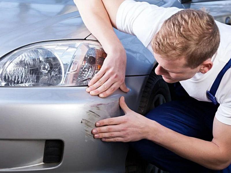 Lakiernik ogląda zadrapania na samochodzie
