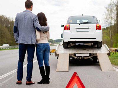 Para przygląda się jak ich samochód ładowany jest na lawetę
