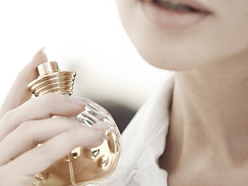 Kobieta spryskuje się perfumami